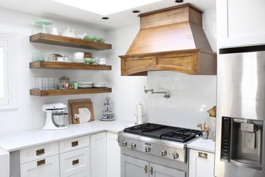 white rustic kitchen with copper vent hood and open shelving