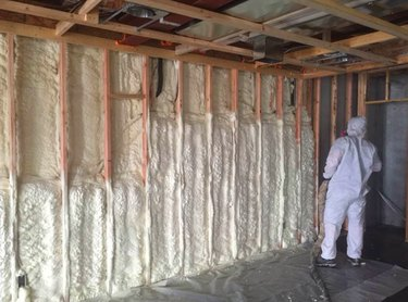 Spraying foam insulation in the basement.