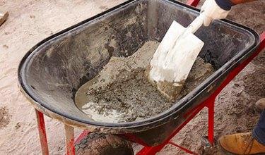 Mixing concrete in a wheelbarrow.