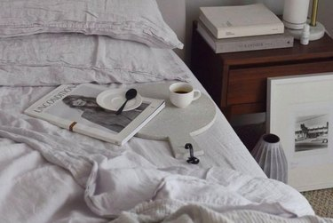 Unmade bed with white linens and a coffee cup