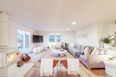 coastal living room with white, gray and off white sectional, jute rug, round white coffee table, white fireplace.