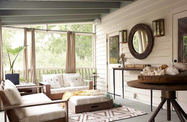 white coastal farmhouse sunroom with wood furniture and patterned rug