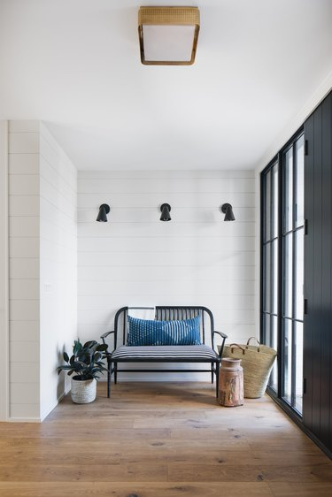 white coastal farmhouse entry with bench and black wall sconces