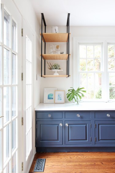 Coastal paint colors in kitchen with navy blue cabinets and open shelving