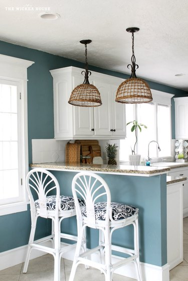 Coastal paint colors in kitchen with white wicker bar stools and teal walls