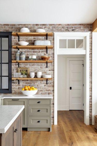 exposed brick kitchen backsplash idea in country kitchen