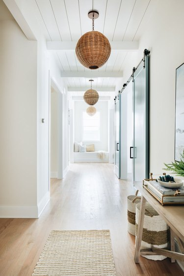 white coastal farmhouse hallway with woven pendant lights and entryway table