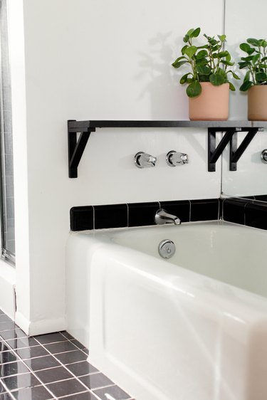 white bathtub with wall-mount silver faucet, black shelf with plant on top, gray square floor tile