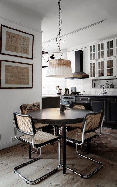 black kitchen cabinets with brass hardware near dining area