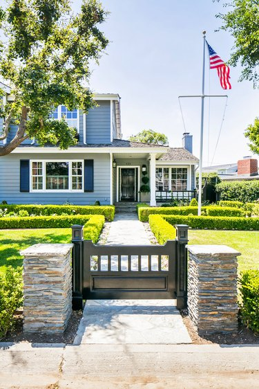 coastal blue home exterior with dark shutters and boxwood hedges