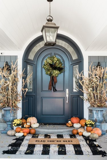 fall porch decor with black front door and checkered mat