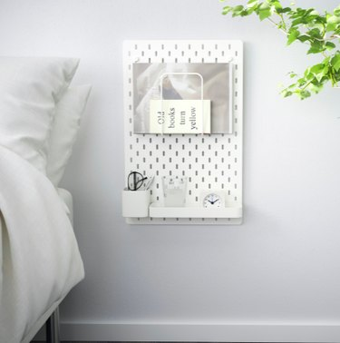 bed with pegboard on the wall nearby