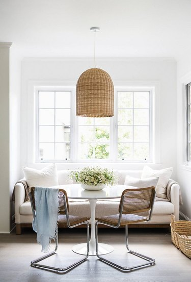 small dining room with caned dining chairs and sofa seating