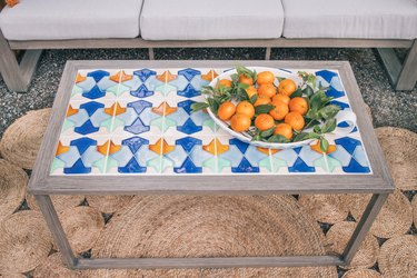 Blue, orange, and white tiled table with basket of oranges