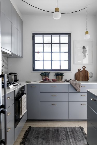 small kitchen layout idea with blueish gray cabinets and hanging pendant lights