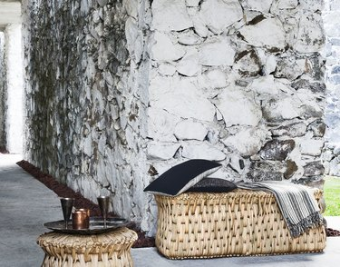 woven side tables and bench with throw pillows and blanket