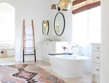 white bathroom with freestanding tub and patterned rug with towel ladder