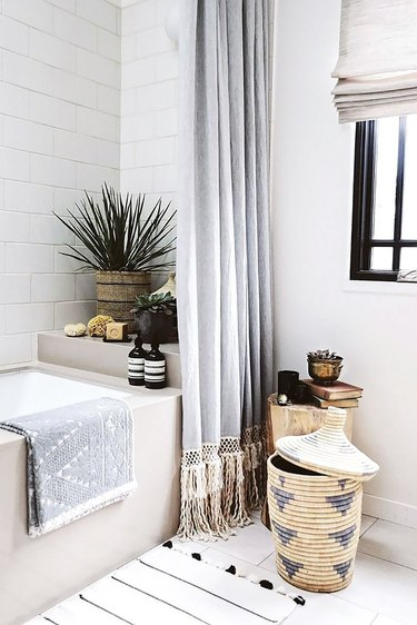 white bohemian bathroom idea with woven baskets and potted plants with Roman shade at window