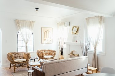 white color idea in living room with rattan lounge chairs, blush sofa and wood accents