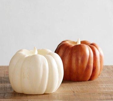 two pumpkin wax candles