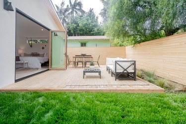 A bedroom with folding glass doors opens up to a backyard with a wood patio, wood horizontal fence, a table with five black chairs and a sofa with a coffee table; green grass and various green plants are planted