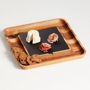 slate and wood board with crackers, cheese, and meats