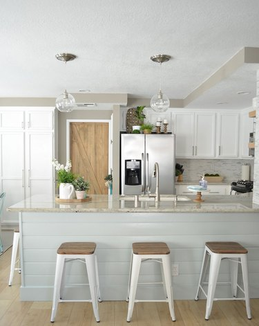 white rustic kitchen with wood barn door and glass pendants over the island