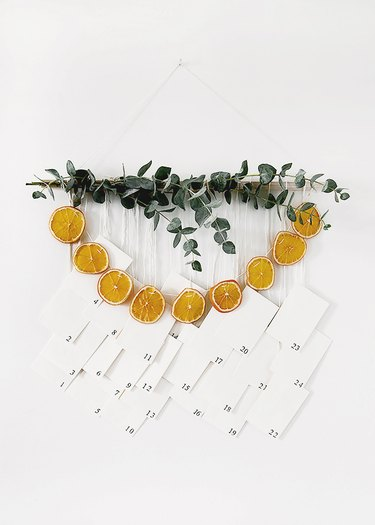 DIY Christmas decorations with white background with advent calendar featuring dried oranges and eucalyptus