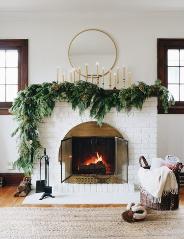 DIY Christmas decorations for white fireplace with mirror above and garland on the mantel
