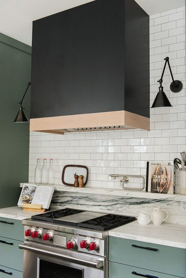 kitchen color idea with black hood and white subway tile and blue-green cabinets