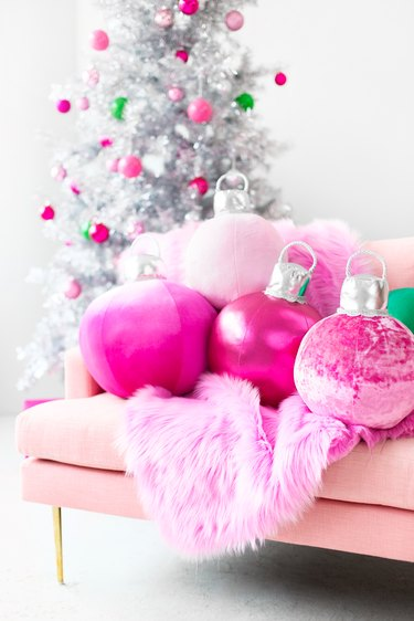 DIY Christmas decorations with pink pillow ornaments on pink sofa