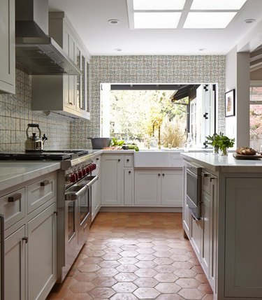 gray cabinets with farmhouse sink and terra cotta kitchen flooring