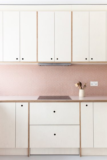 pink kitchen with pink tile backsplash and white cabinets