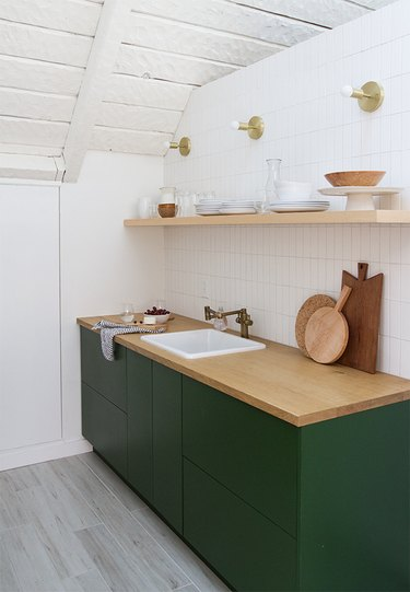 Simple white subway tile backsplash in minimalist kitchen with green cabinets and wood countertop