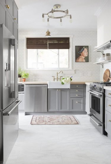 gray and white kitchen with dark gray cabinetry and marble vinyl floor