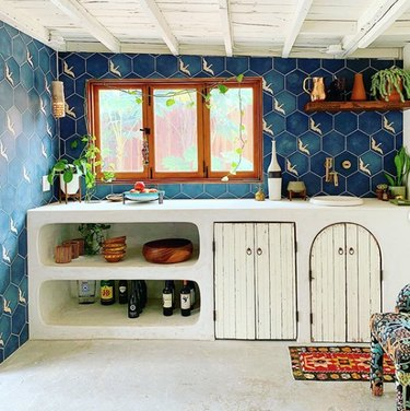 bohemian kitchen color idea with blue wall tile and white countertop and cabinets