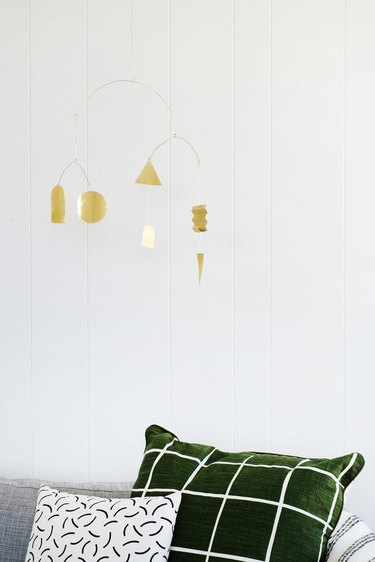 brass mobile hanging above a couch