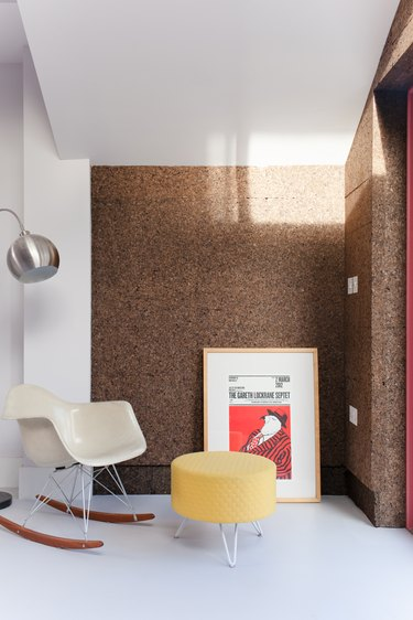 midcentury living room with cork walls and eames chair