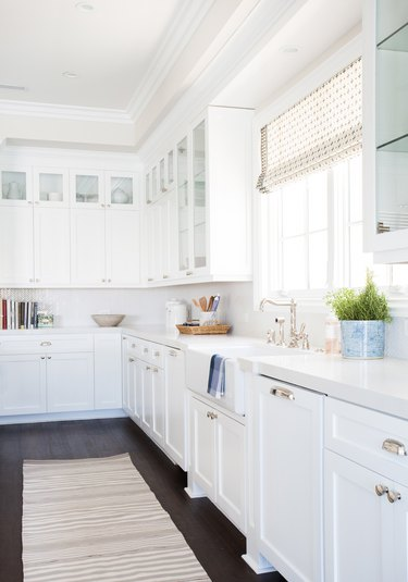 transitional kitchen style with wood flooring and white cabinets