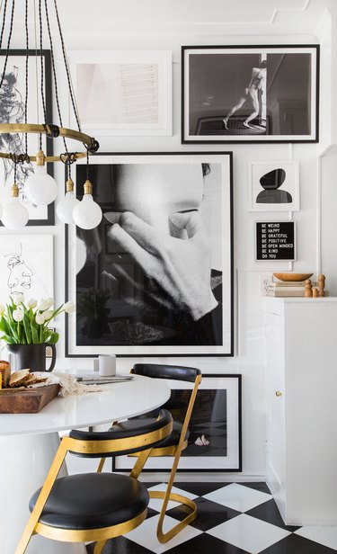 black and white kitchen vinyl flooring with gallery wall and white cabinets