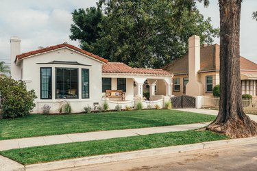 Spanish-style home with large tree in the front and green grass