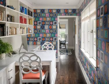 Home Office for Two White built in face to face desk with book shelves and wallpaper.