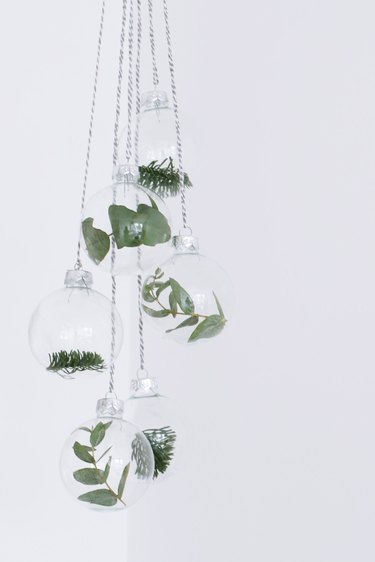 Glass ornaments with greenery inside