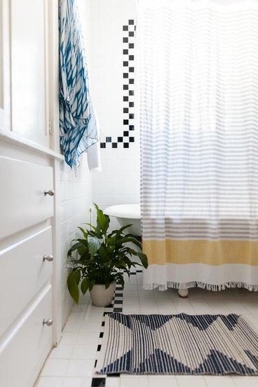claw-foot bathtub/shower, shower curtain and decorative floor mat