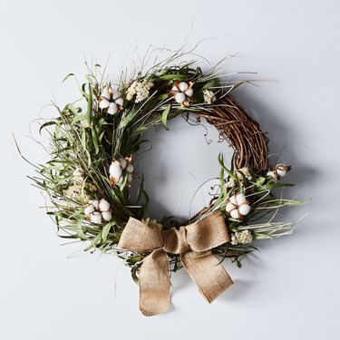 farmhouse Christmas decor with grapevine wreath with greenery, cotton buds, and burlap bow