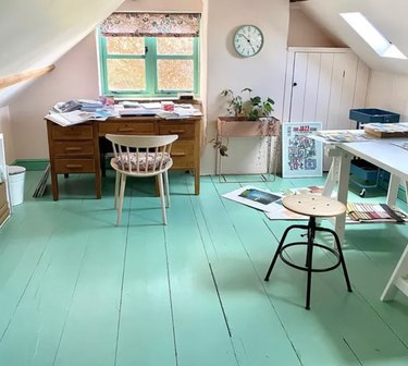 Home Office for Two Attic office with painted turquoise wood floors, vintage desk, stool, wall clock.