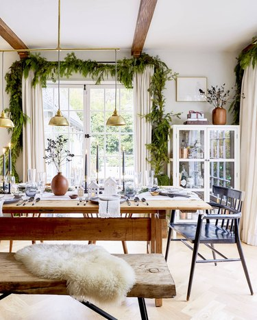 Christmas centerpiece in dining room with table and brass pendants