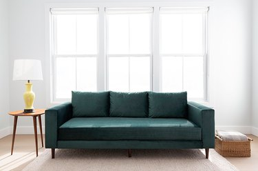 green couch near table with lamp and windows
