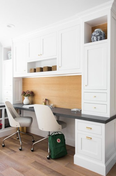 Home Office for Two White built in cabinets with desk, white desk chairs.