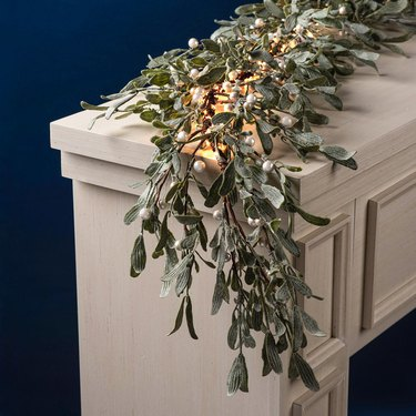 farmhouse Christmas decor with mistletoe garland with lights and pearly berries